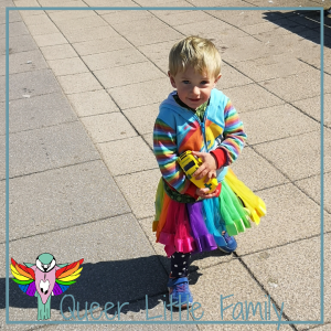 Snappy in a rainbow tutu and holding a toy ambulance.