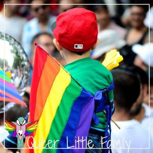 a kid facing away from the camera, at a pride event.