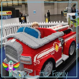 Snappy sitting in a lego fire engine from Paw Patrol.